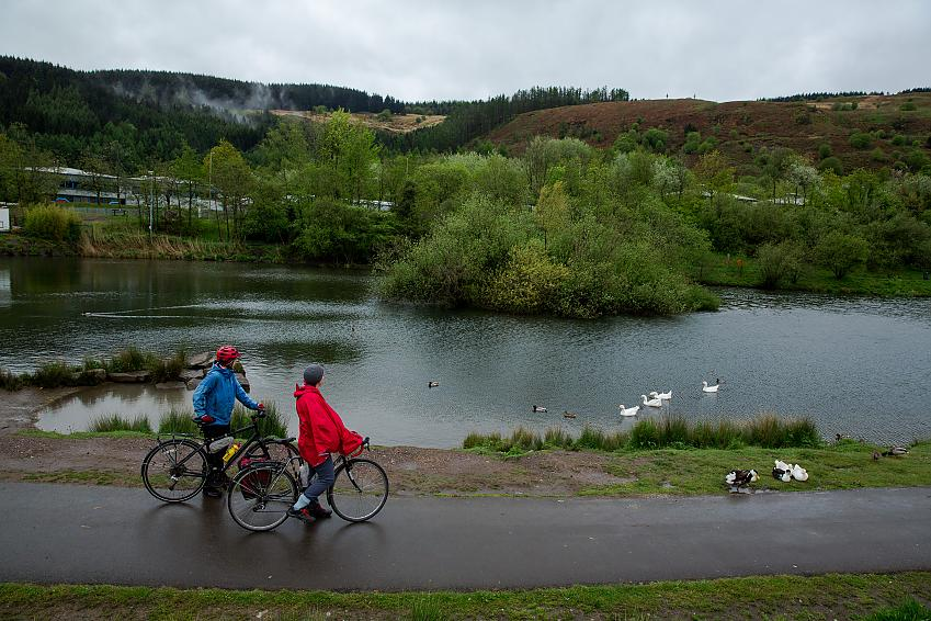 Two women stand with bikes looking over a lake