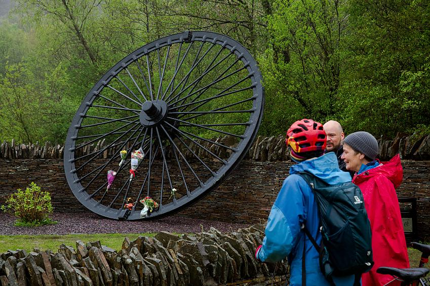 People stand beside a large black memorial wheel with flowers tied to it