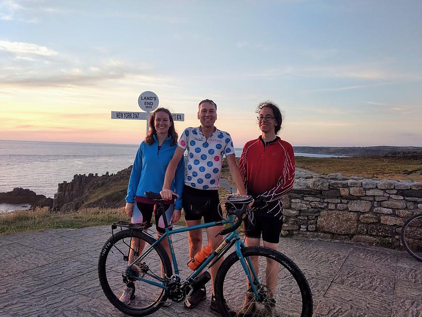A man posing with his son and daughter and bicycle at Land's End
