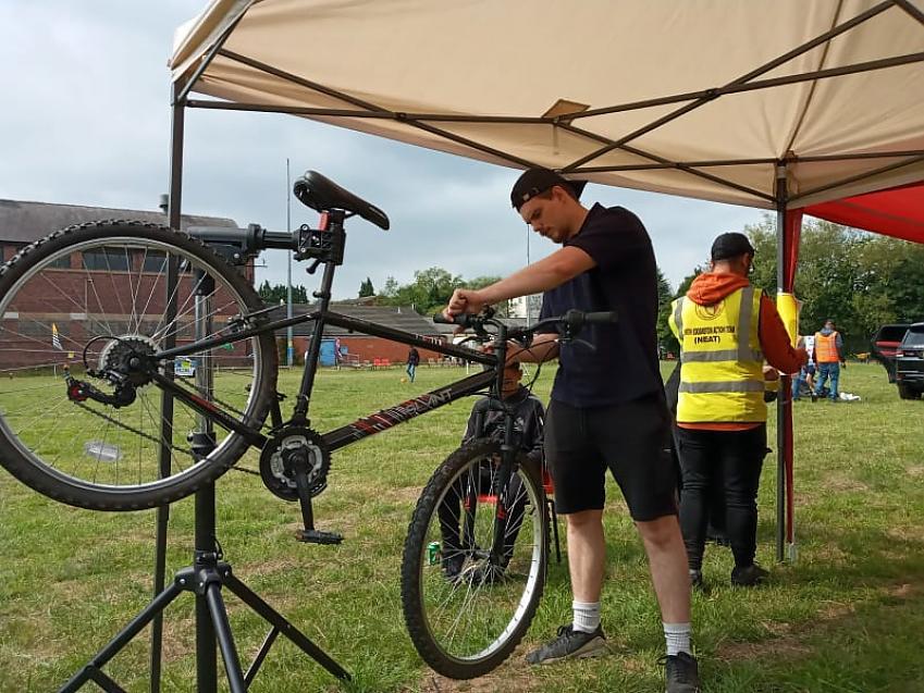 A man fixes a bicycle under a gazebo