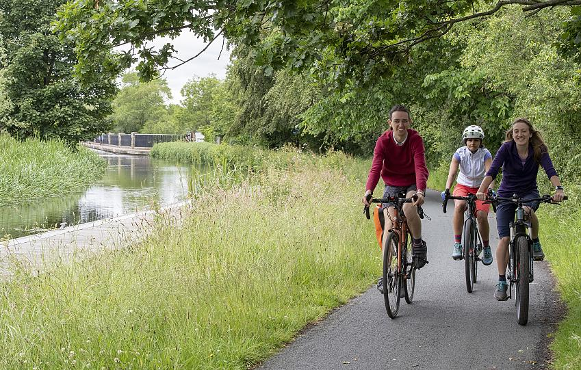 Three people cycling along a canal path