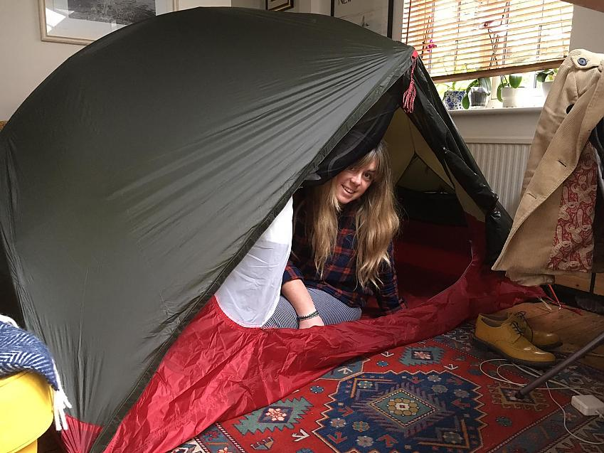 A woman is camping in her living room