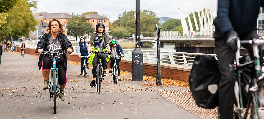 Cyclists riding by the river in Cardiff