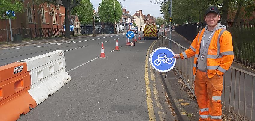 Highway worker holds cycling sign next to temporary cycle lane