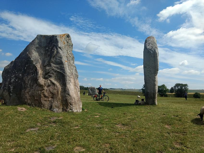 A man poses with his bicycle among Neolithic monuments while sheep graze around him