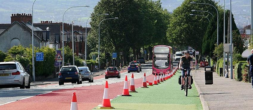 Woman cycling along a temporary cycle lane marked with cones
