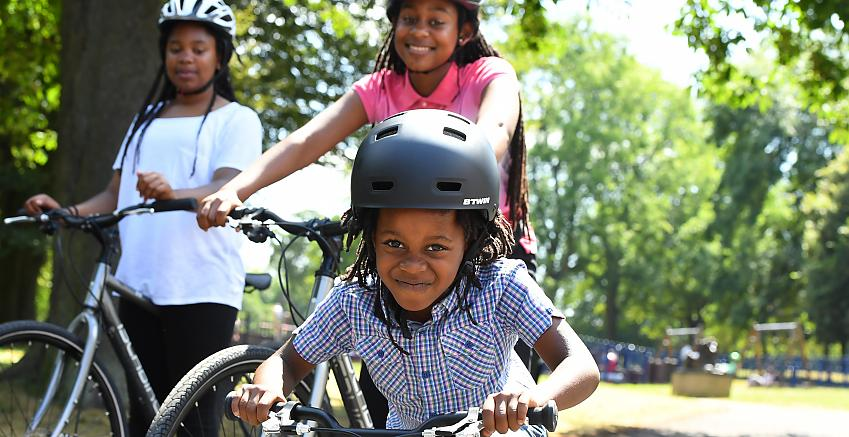A young boy on a bike grinning with two girls on bikes beside him