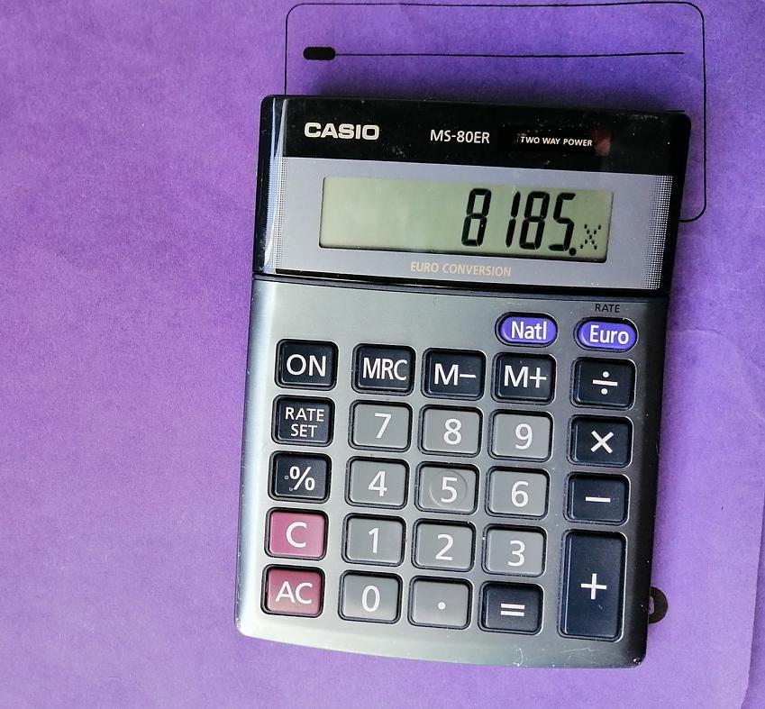A calculator displaying the value 8185 placed atop a purple folder