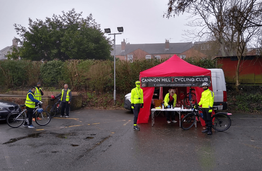 A distant shot of a people under a gazebo on a wet looking day, two cyclists in yellow jackets appear to be heading to visit the stand