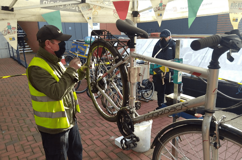 An outdoor cycle repair session, a blue barge with yellow lettering can be seen in the background