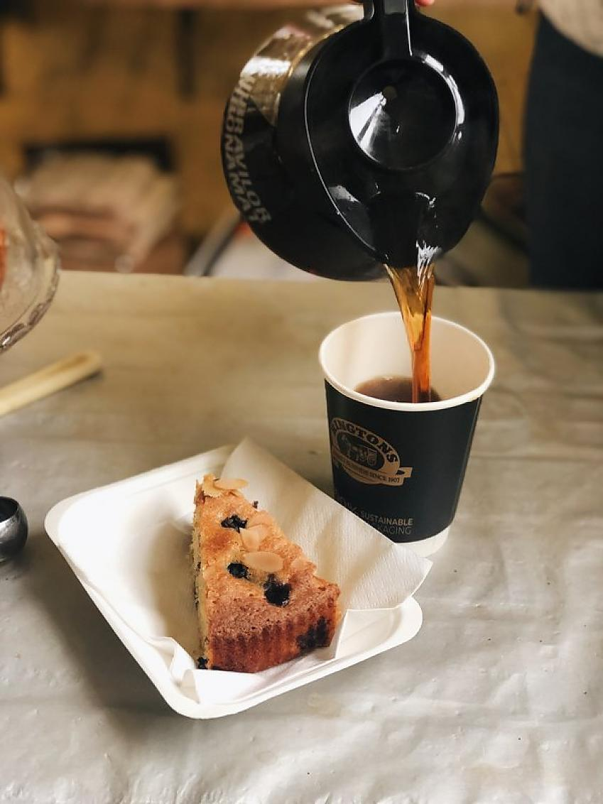 A cup of coffee being poured from a filter pot and a piece of cake on a table