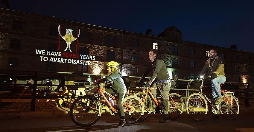 """People cycle past a projection on Holyrood building saying """"We have seven years to avert disaster"""""""