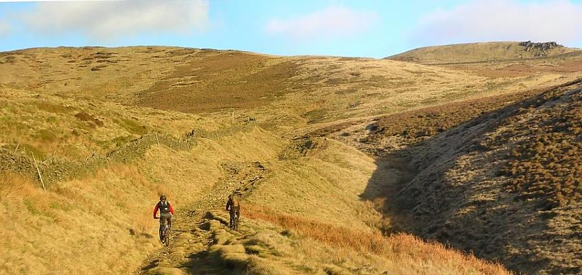 Two mountain bikers riding across a moorland trail