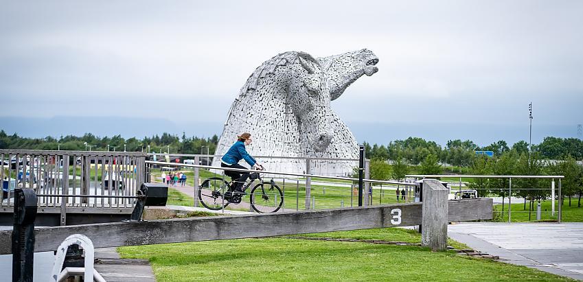 Woman cycles past Falkirk Kelpies