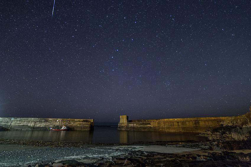 Dark starry sky above a harbour