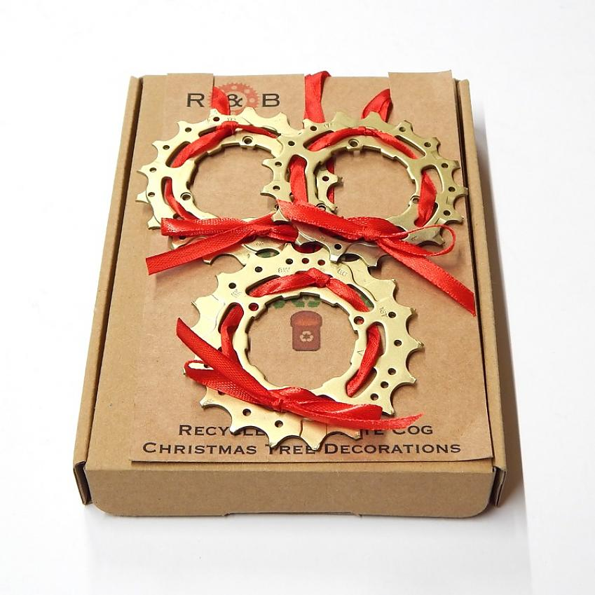 Three Christmas decorations made from an old cassette cog with red ribbon tied through it
