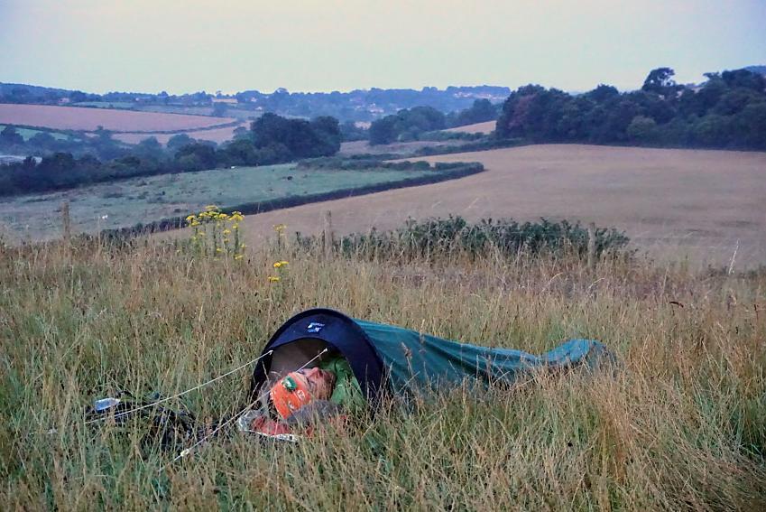 A man sleeps in a hooped bivvy bag