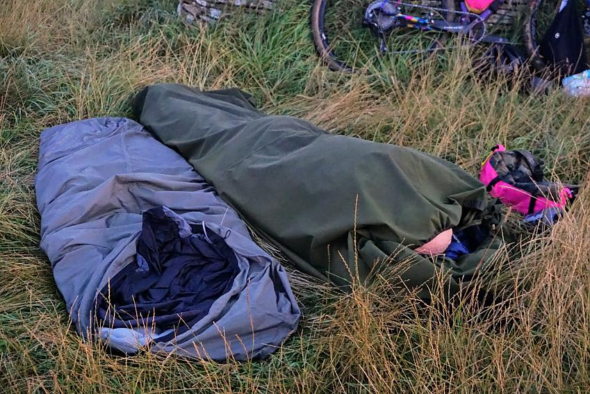 Two bivvy bags with one sleeper laid out in a field