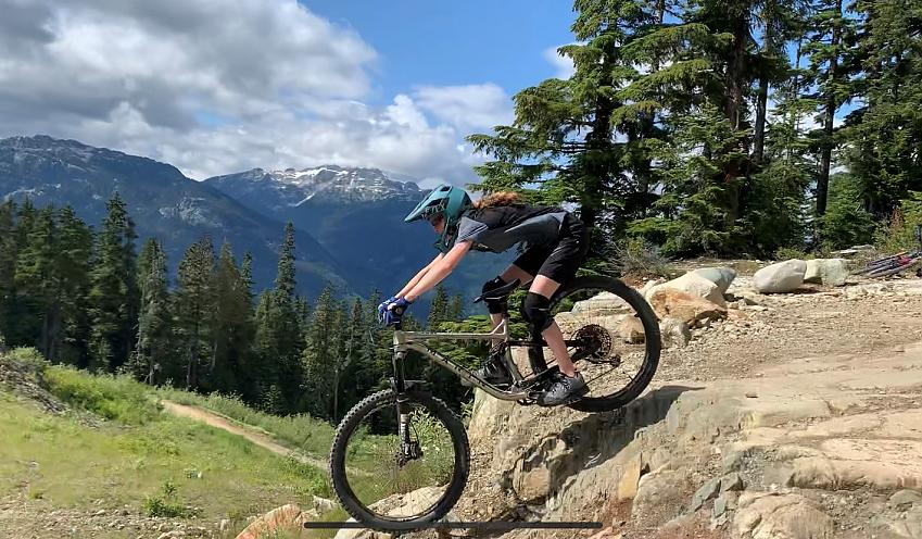 Eme tackling a rock drop in Whistler, Canada, with the Rockies in the background