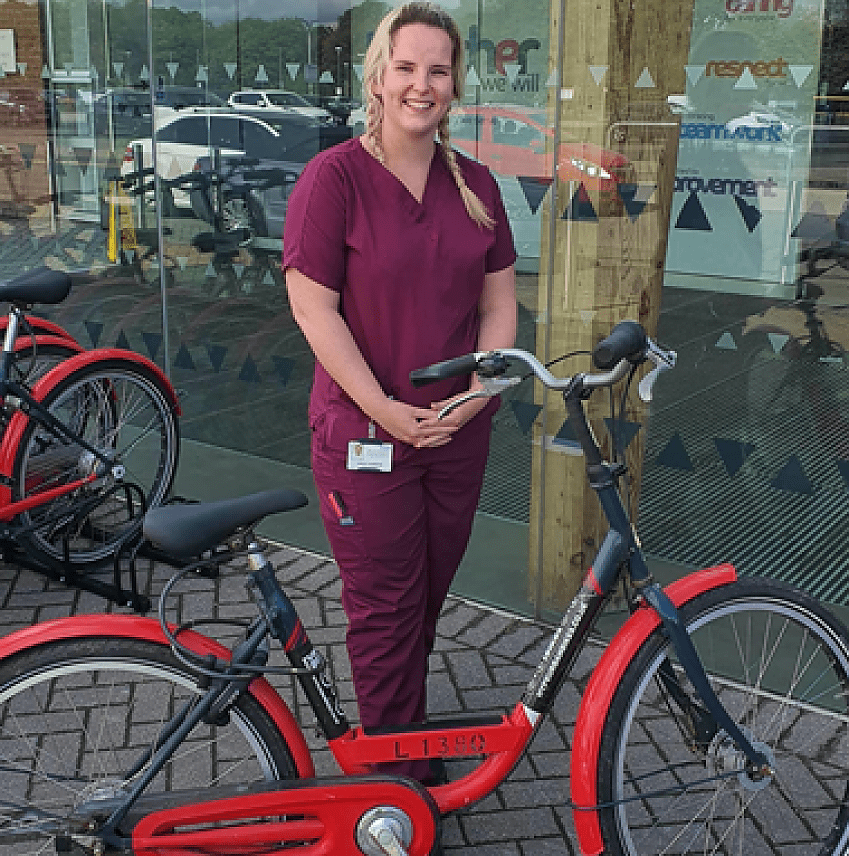 A blonde woman with purple healthcare workers' uniform stood with a red bicycle