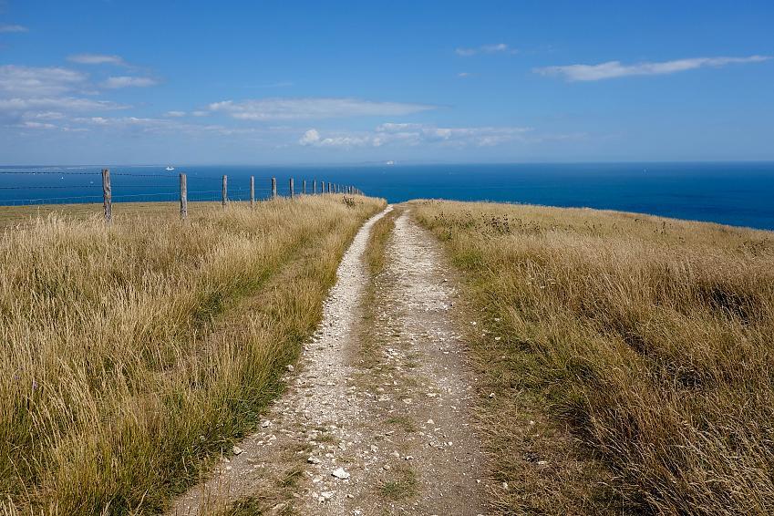 Gravel track heading towards blue sea