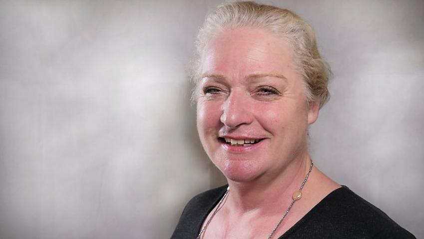 A woman with blonde/grey hair wearing a black top positioned in front of a white backdrop