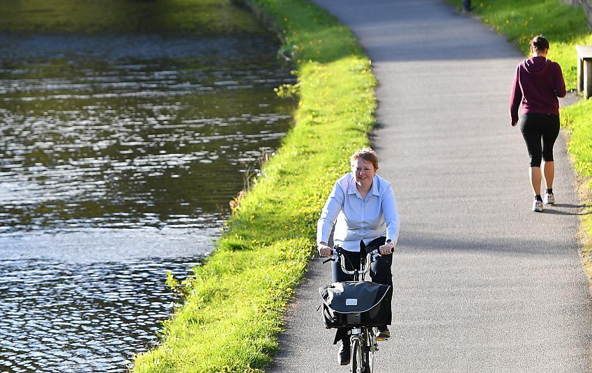 Woman cycling along a canal