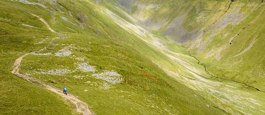 Mountain biker riding beside deep valley