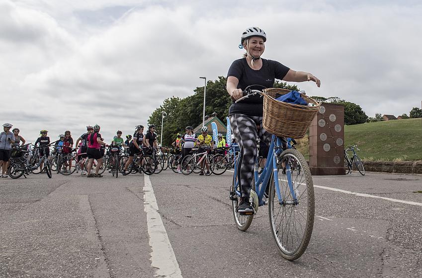 A woman on a blue bike with a basket