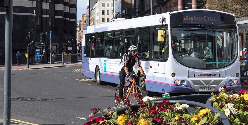 Man cycling past bus