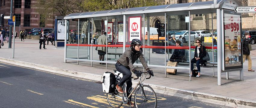 Man cycling past bus stop