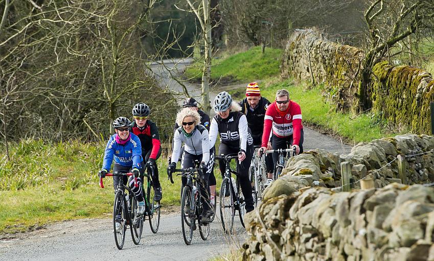 Cycling club riding along a lane