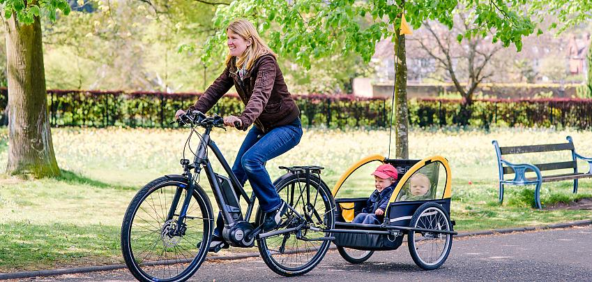 Woman cycling with two children in a trailer