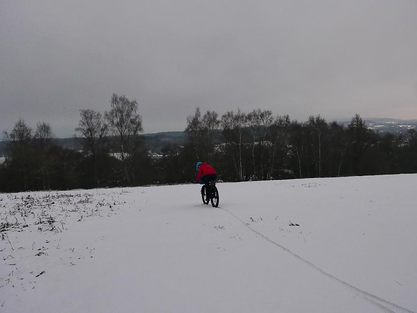 Cyclist heading down a snowy hill
