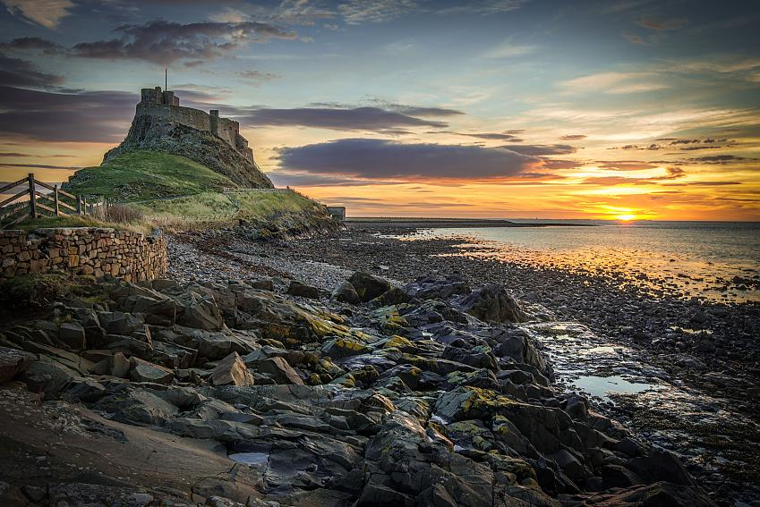 Castle on a high hill on an island, with a rocky coastline in the foreground