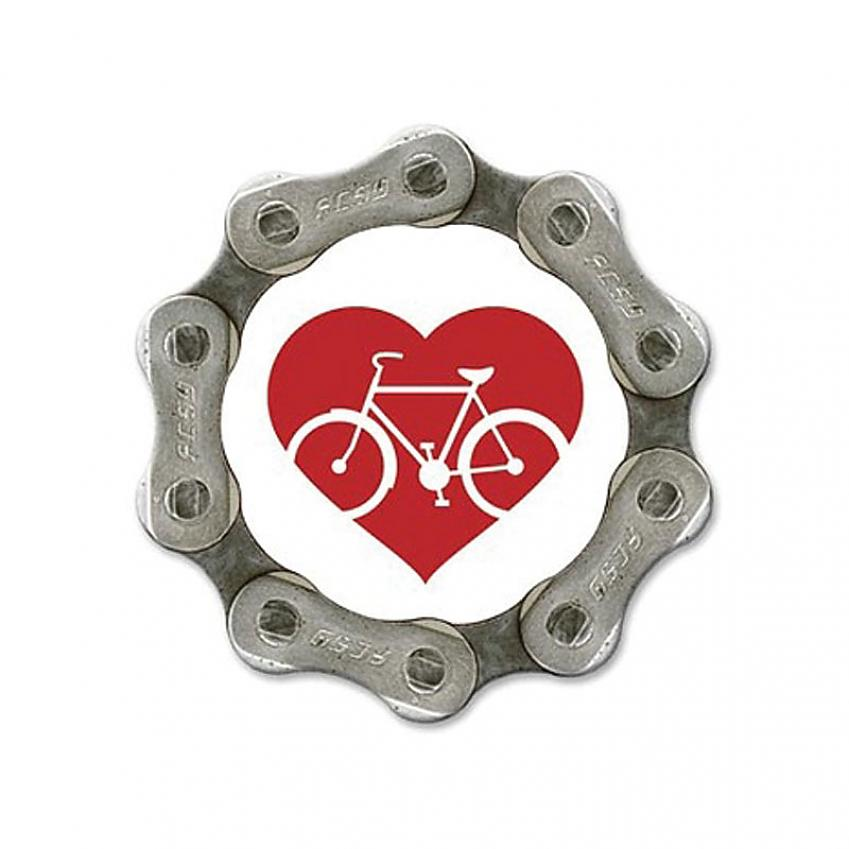 A fridge magnet made from bicycle cog with a red heart logo in the centre