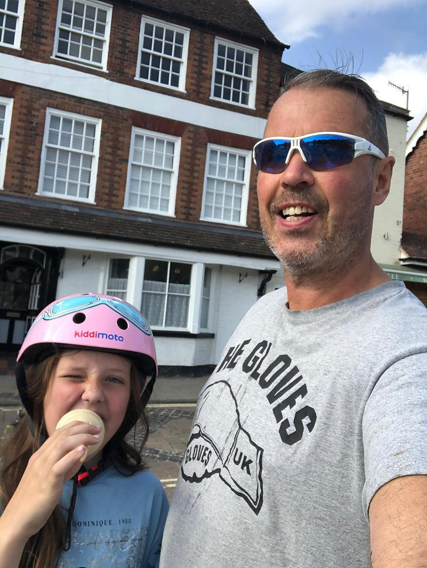 A young girl wearing a pink cycle helmet eating an ice cream with her father, stood outside a historic building