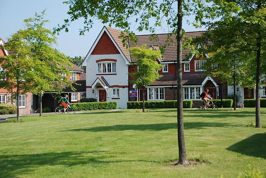 Someone cycling past a park on a housing estate