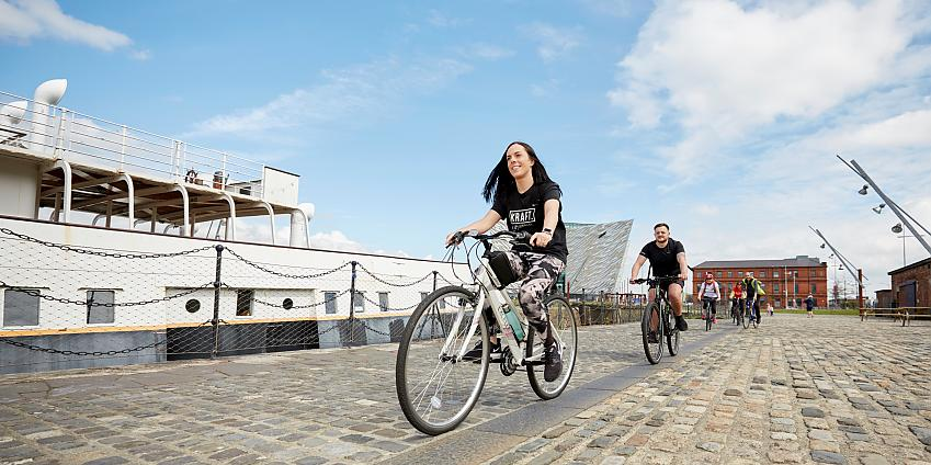 Woman cycles past SS Nomadic ship in Belfast