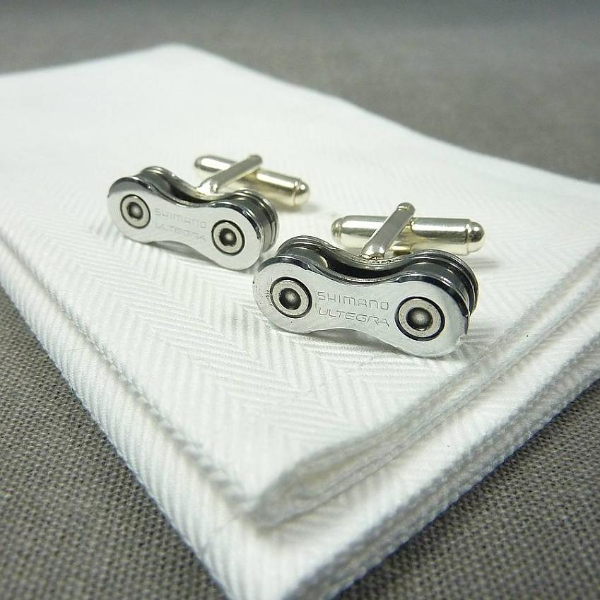 A set of silver cufflinks on a white towel