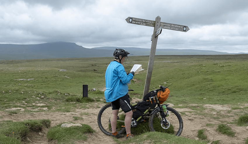 A cyclists stops to look at a map at a crossroads sign in the countryside