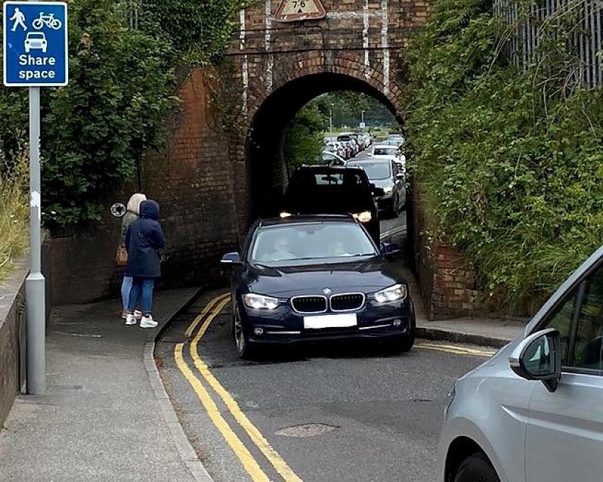 Cars queue up to pass under the bridge while pedestrians wait