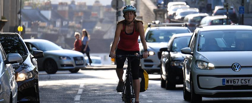 Woman cycling on cycle lane through heavy traffic