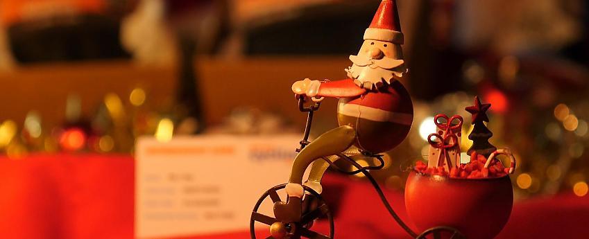 A wooden Santa toy in front of a low-lit festive scene