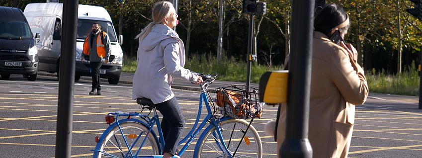 Woman riding a Dutch bicycle at a junction