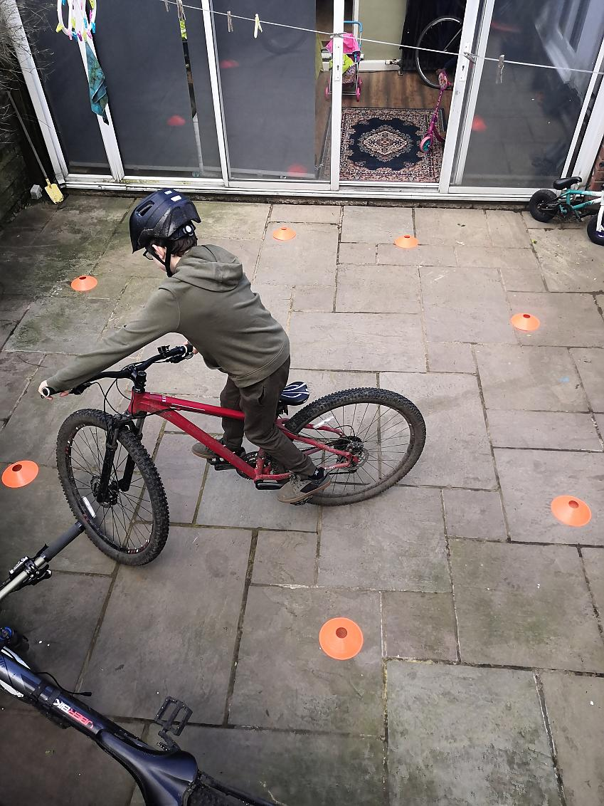 A boy on a mountain bike riding between some cones