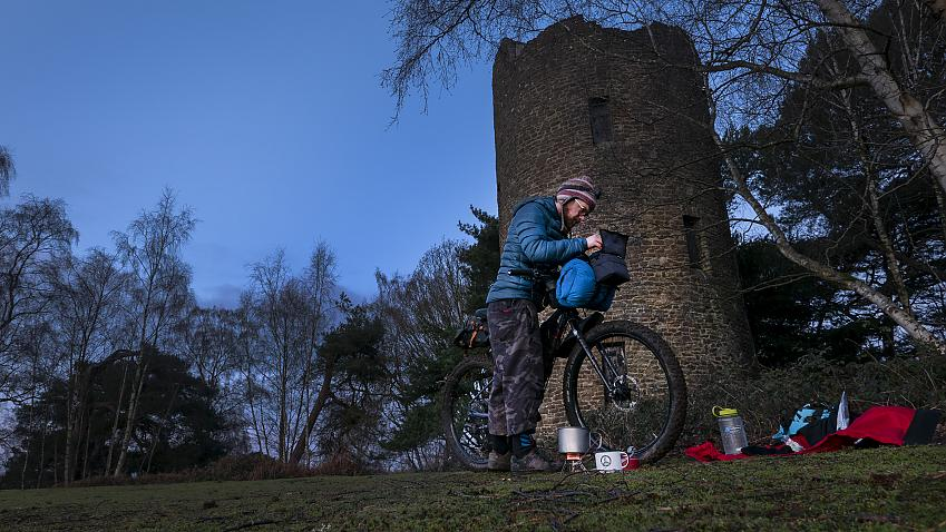 Cyclist packing up their bike for bikepacking in the dawn