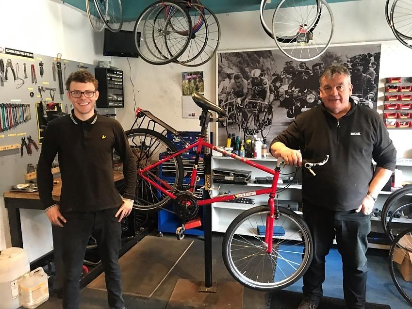 Two mechanics with a repaired bike in a bike shop