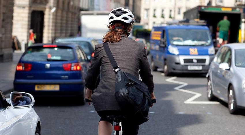 Lady cycling in suit with helmet