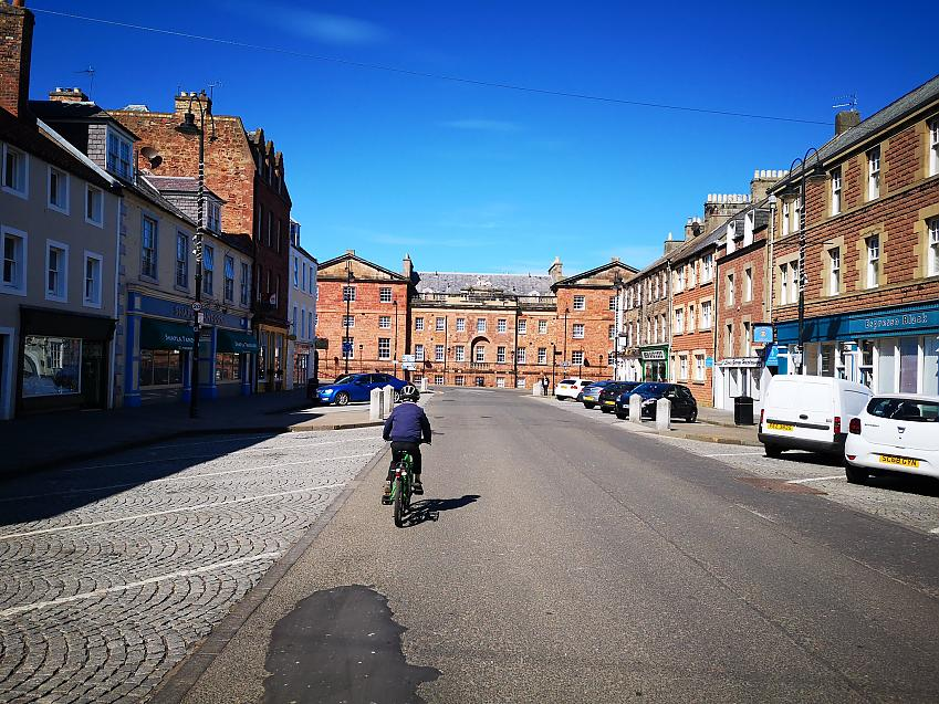 A small child cycling on an empty high street
